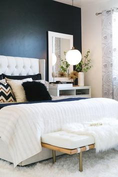 HGTV features this stylish contemporary bedroom with a black accent wall, white linens and funky patterned pillows.