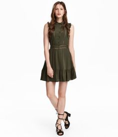 Dark khaki green. Short dress in woven viscose fabric. Small ruffled sleeves, collar, and buttons at top. Inset lace trim at front and at waist. Flared
