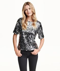 Short-sleeved blouse in sequin-embroidered mesh with a slightly wider neckline. Jersey lining.