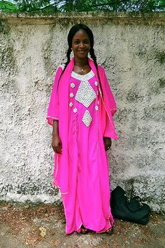 Big Picture - Africa: woman in pink dress standing in front of wall Dress Stand, Pictures Of The Week, Sierra Leone, Pretty In Pink, Pink Dress, Kimono Top, Cover Up, Sari, Street Style