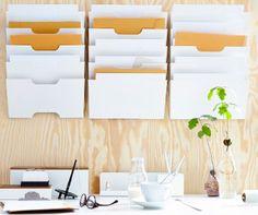 Escritorio delante de un panel de madera con un tablón de anuncios y almacenaje de pared de IKEA.