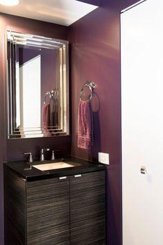 Bathroom: Plum Perfect. bathroom color. dark bathroom. purple bathroom. metal mirror frame. chrome finish towel holder. black vanity top. dark vanity storage.