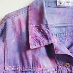 Casaco em jeans azul médio com descoloração irregular e tingimento em rosa antigo. Pespontos e aplicação de fio com flores azuis. Mandalas e crochê também aplicados. Fechamento com botões em metal. Manga longa.