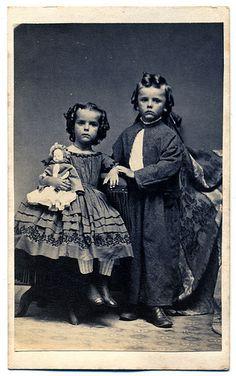 Vintage Studio Portrait: Civil War Era siblings with curled hair. Little girl is holding her favorite doll.