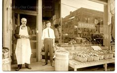 ID#0113 Date: 1900-1920. This photo is from a postcard of the H.B. Dobyns grocery store. One of the individuals in the photo is identified on the back as Mr. Severy--the business became the Severy and Sage grocery store after it was H. B. Dobyns. A reflection of Watson's Hardware across the street can be seen in the window.   Participant: John P. Gorske. Additional Sources: Oberlin Heritage Center: Historic Preservation commission survey, 1998; Fred Maddock files.