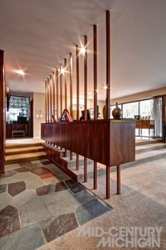 Architect Unknown - 1958. Materials such as slate, marble, brick, cherry and rosewood compose the interior surfaces.  The formal living and dining area make the most of the materials, with exposed brick walls and a long, suspended rosewood-clad credenza spans the change in levels, supported by a series of balusters which are anchored to the floor and ceiling.
