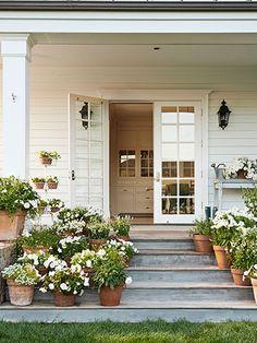White flowers—including salvia, violas, petunias, begonias, and lantana—adorn the charming side porch of this California farmhouse. LOVE!