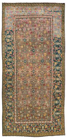 A Samarkand rug BB4392 - An early 20th century Samarkand (Khotan) rug, the abrashed brownish purple field with an overall polychrome trellis ...