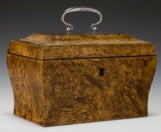 An early 19th century teacaddy, veneered in a burr-wood and treated to appear as mulberry, within, a pair of compartments with similarly veneered covers over a further pair of sycamore wood presses and with cut steel handles to all lids.  French circa 1800.