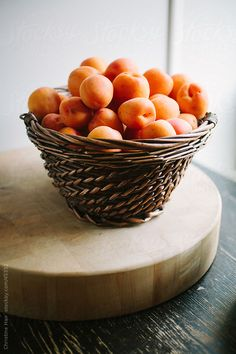 Fresh apricots sitting in a basket on a kitchen counter  by christineshoots   Stocksy United