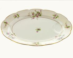 This lovely, vintage Theodore Haviland platter shows lovely sprays of pink roses and green spray. The gently scalloped edges are outlined in gold with a corresponding gold trim at the base. This large, 16 meat platter has a juice well to capture those tasty juices. If you love cottage style porcelain, this pretty platter is for you. The marks lead me to think this vintage platter was produced sometime between 1920 and 1945. The horseshoe mark was used 1920-1936, and the shield between 1936…