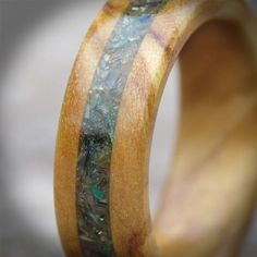 This is our Spanish Olive wood and Abalone shell inlay ring. Since its introduction in 2014 it has been one of our most popular wooden engagement rings to date.To find out more visit the UK's original wooden ring maker at www.wooden-rings.com
