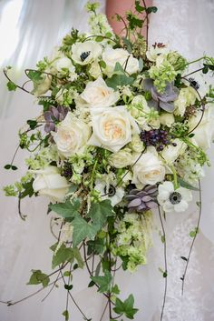 Cascading bridal bouquet of white roses, poppies, ivy and succulents at a Disney Fairy Tale Wedding