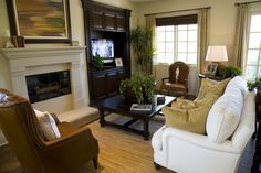 Rich leather on two chairs in this room stand out next to white couch and fireplace, with dark wood shelving and coffee table.