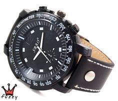 Ρολόι ανδρικό σε μαύρο χρώμα με λευκές λεπτομέρειες σε όλη την κάσα και στο εσωτερικό του.  Λουράκι από γνήσιο δέρμα σε μαύρο με λευκές ραφές. Καντράν 50 mm.