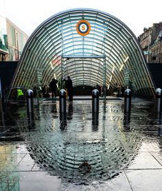 The new entrance to St Enoch's Underground station in Glasgow, reflected on the rainy pavement to give the impression of a fingerprint.