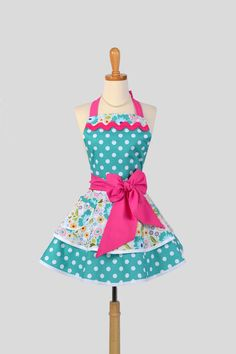 Muy lindo mandil retro en otra combinación de colores Ruffled Retro Apron / Handmade Flirty Full Womens Apron in Riley Blake Teal Dots and Floral Cute Cute Apron. $45.00, via Etsy.