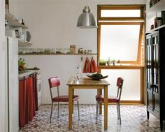 """A proprietária desse apartamento pediu à arquiteta Claudia Mota, do Ateliê Urbano, """"uma cozinha com a cara de avó"""". O ladrilho hidráulico no piso dá um ar antiguinho ao espaço. Ali, nada de armários. Como o orçamento era enxuto, o tecido colorido faz as vezes de cortina na bancada. Já a prateleira de compensado naval revestida de laminado apóia os potes de temperos."""