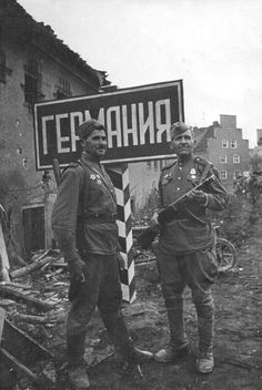 Two middle aged Soviet soldiers, armed with sub machine guns, pose on the old Polish-German demarcation line as the Soviet advance crosses into the Reich, October 1944.