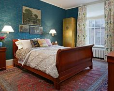 Eclectic bedroom. Blue wallpaper, oriental faded rug, lots of wooden furniture, wall art, cosy bedding.