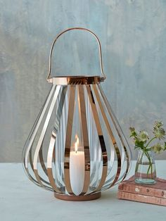 Place a pillar candle inside our striking copper finish lantern and the graphic vertical struts of metal will cast enticing shadows all around the room.