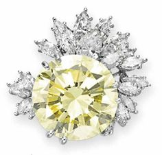 A COLORED DIAMOND RING   Set with a circular-cut fancy light yellow diamond of approx. 21.37 carats, extending a spray of pear and marquise-cut diamonds, mounted in platinum.