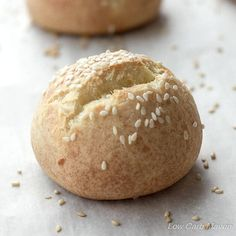 Round low carb roll with sesame seeds and a split top on a piece of parchment with another roll in the background.