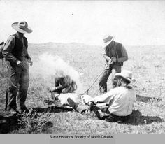 1885: Four cowboys branding calves, Medora, Dakota Territory. Two cowboys hold down a calf while a third cowboy brands it, likely with the brand of the Marquis de Mores. A fourth cowboy looks on. Smoke rises from the branding.