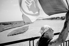 A man carrying an American Indian Movement flag across the Veterans Memorial Bridge in Bismarck, N.D., during a demonstration against the pipeline. Aug. 8 2016 (NYT Photo: Annabelle Marcovici