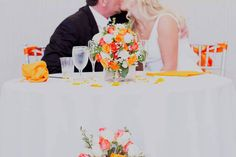 Love this white sweetheart table with the bright florals!!