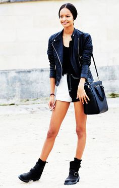 Malaika Firth in a black leather jacket paired with a tank top, black and white denim shorts, and black boots