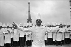 Paris-Gathering of 400 well-known French cooks in front of the Eiffel Tower . In foreground stands the famous chef Paul Bocuse, 1976. (c) Jean Gaumy /  Magnum Photos.