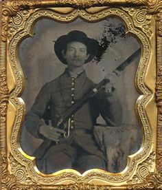 Armed Confederate Private 1/6 plate  ambrotype of a Confederate private in full uniform with his musket and a nifty black hat. Full case with split hinge.