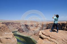 An asian woman taking pictures at the horseshoe bend