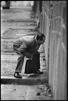 West Berliner looking into East Berlin through a crack in the Berlin Wall at the time of its construction. West Berlin, Germany, November 1961. Photo by Don McCullin