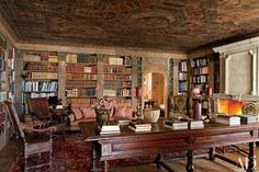 A 16th-century Italian painted ceiling crowns the pine-paneled living room/library of a house in Saint Moritz, Switzerland, with architecture and interior design by Studio Peregalli.