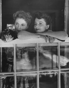 Sisters and frequent rivals Joan Fontaine and Olivia de Havilland share a family moment as they look out over Beverly Hills from Fontaine's home in 1942.