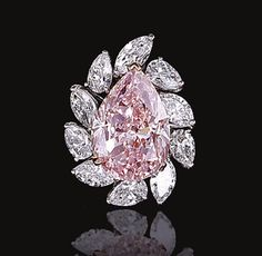 IMPORTANT FANCY LIGHT PINK DIAMOND RING.  Claw-set with a fancy light pink pear-shaped diamond weighing 9.05 carats, bordered by marquise- and pear-shaped stones, mounted in white and rose gold,  size 49.