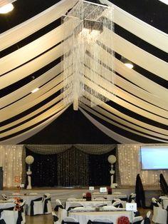 fundraiser gala decor-ceiling chandelier, black/white backdrop with iridescent beaded curtains www.grapevineweddingrentals.com