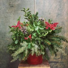 "Red tin butterfly table topper. Mixed greens holly frosted pine cones. 14""h x 14""w. $22. #holiday"