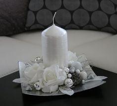 Vánoční svícínek - bílostříbrný Něžný vánoční svícen v bílých a stříbrných odstínech, na stříbrném tácku s bílou drápanou svíčkou, zdobený květy růžiček, hvězdičkami, listy a skleněnými kouličkami. Velikost svícnu - výška cca 13 cm, šířka cca 19x19 cm.