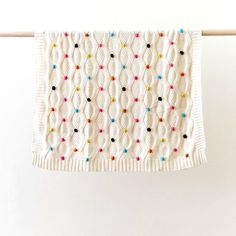 A gorgeous off white baby blanket with coloured (pink, orange, yellow, green, black) pom poms dotted over one side. Perfect for bassinet, cradle, c...