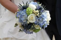 The heavenly Bridal Bouquet of White Peonies, Blue Eryngium Thistles, Pale Green Viburnum Opulus, Blue Hydrangeas, Viburnum Tinnus, Gypsophilia and Wax Flower Blosson