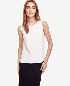 "Impeccably tailored with a soft knit front and sleek woven back, this piece is a modern must-have. Boatneck. Sleeveless. Woven back. Side slits. 22 3/4"" long."