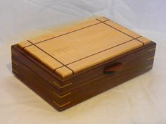 Made of solid walnut and maple with mitered corners with maple splines. the interior dividers are maple and hand fit. The box is lined in black velvet. Size 12 1/2 x 8 x 4