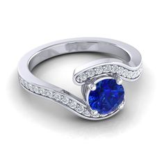 She will have you spellbound with a single glance. This ring with its center stone placed between two arches is a beautiful design. Spellbound and captivating as the gems show off the center stone.