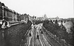 A view from Waterloo Bridge showing horsedrawn carts driving along Embankment next to the Thames in London, circa 1880. St Paul's Cathedral is in the background.  Fascinating early photographs of London