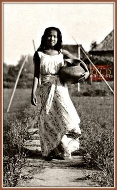 """""""Photograph of a Filipina standing outside holding a clay pot. She wears a white sleeveless top and a floral print skirt. In the distance behind her on the right hand side of the photo is a nipa hut.""""  Date: September, 1925  Source: Maryknoll Mission   =Gabriela= Philippines Country, Philippines People, Philippines Culture, Manila Philippines, Melanesian People, Old Photos, Vintage Photos, Sampaguita, Filipino Culture"""