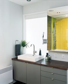 crumbled due to a weak foundation, architect Marc-André Plasse eked out another 500 square feet with a clever multilevel addition on one side. Tiles from Ramacieri-Soligo brighten the small bathroom, off the hall. Photo by Alexi Hobbs.