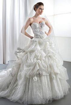 Brides: Demetrios - Young Sophisticates. Organza and lace strapless ball gown with a jewel encrusted bodice embellished with 3 dimensional flowers. Bustled skirt features a lace, underlay, scattered flowers and attached train. Available in white, and ivory. (also available as separates).